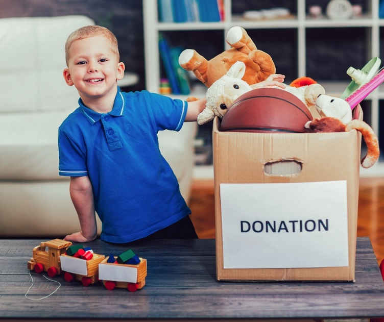 little boy with box of donated toys